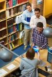 Studenti maturi al contatore nella biblioteca di istituto universitario Fotografia Stock