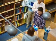 Studenti maturi al contatore nella biblioteca di istituto universitario Immagine Stock Libera da Diritti