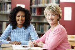 Studenti maturi che lavorano nella biblioteca Fotografia Stock
