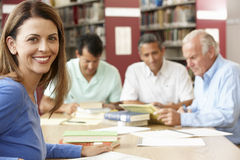 Studenti maturi che lavorano nella biblioteca Immagini Stock