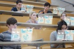 Studenti messi a fuoco nel corridoio di conferenza che lavora alla loro linguetta futuristica Immagine Stock Libera da Diritti