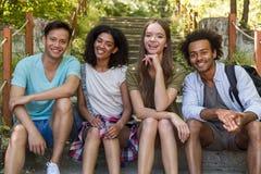 Studenti multietnici allegri degli amici all'aperto che si siedono sulla scala Fotografie Stock