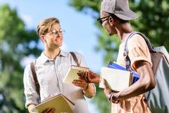Studenti multietnici bei che tengono i libri e che se esaminano in parco Fotografie Stock Libere da Diritti