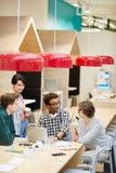 Studenti multietnici che discutono progetto dell'università in caffè immagine stock