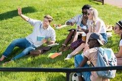 Studenti multietnici che riposano insieme sull'erba verde in parco Immagine Stock Libera da Diritti