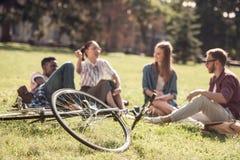 Studenti multietnici che riposano sull'erba Immagini Stock Libere da Diritti