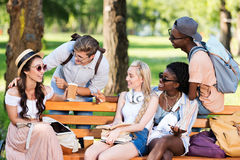 Studenti multietnici che tengono i libri ed i dispositivi digitali mentre interagendo nel parco Immagini Stock