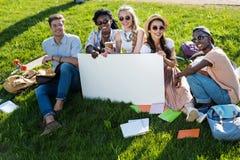 Studenti multietnici che tengono insegna in bianco mentre sedendosi sull'erba verde Fotografie Stock Libere da Diritti