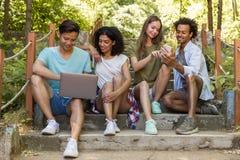 Studenti multietnici degli amici all'aperto facendo uso del telefono cellulare e del computer portatile Fotografie Stock