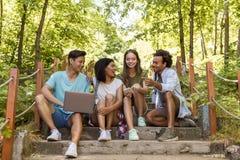 Studenti multietnici degli amici all'aperto facendo uso del telefono cellulare e del computer portatile Fotografia Stock Libera da Diritti