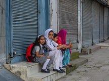 Studenti musulmani che aspettano il bus sulla via fotografia stock