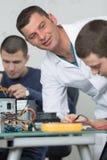 Studenti nell'elaborazione elettronica della riparazione di tecnologia Fotografia Stock Libera da Diritti