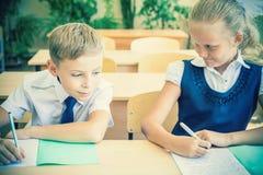 Studenti o compagni di classe nell'aula della scuola che si siede insieme allo scrittorio Fotografia Stock