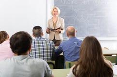 Studenti parlanti dell'insegnante in università Immagini Stock