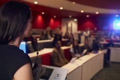 Studenti parlanti della donna nel teatro di conferenza, priorità alta del fuoco Fotografia Stock Libera da Diritti