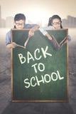 Studenti primari dietro testo di nuovo alla scuola Fotografia Stock Libera da Diritti