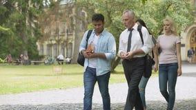 Studenti razza mista ed insegnante che camminano nel parco e che parlano, istruzione superiore stock footage
