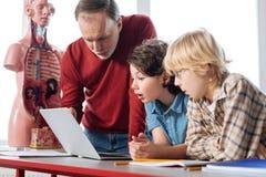 Studenti risoluti emozionanti che mostrano i risultati al loro insegnante Fotografie Stock