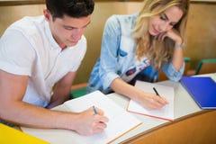 Studenti seri che scrivono durante la classe Fotografia Stock