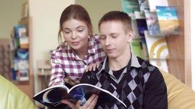 Studenti sorridenti in biblioteca che godono di un libro scelto video d archivio