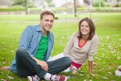 Studenti sorridenti casuali che si siedono sull'erba Fotografie Stock Libere da Diritti