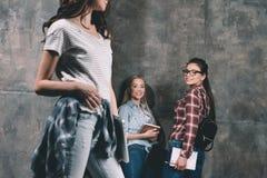 Studenti sorridenti che considerano ragazza che sta con il computer portatile Fotografia Stock