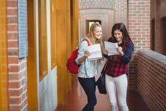 Studenti sorridenti che esaminano i risultati Fotografia Stock