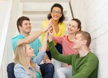 Studenti sorridenti che fanno seduta di gesto di livello cinque Immagini Stock