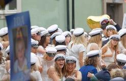 Studenti sorridenti che indossano i cappucci bianchi di graduazione dopo la graduazione Immagini Stock Libere da Diritti