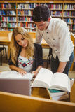 Studenti sorridenti che lavorano insieme mentre sedendosi alla tavola Fotografia Stock