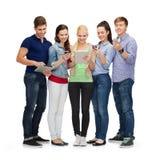 Studenti sorridenti che per mezzo degli smartphones e del pc della compressa Fotografia Stock