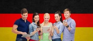 Studenti sorridenti che per mezzo degli smartphones e del pc della compressa Fotografie Stock Libere da Diritti