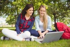Studenti sorridenti che per mezzo del computer portatile Immagini Stock Libere da Diritti