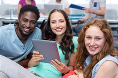 Studenti sorridenti che per mezzo della compressa digitale Fotografie Stock