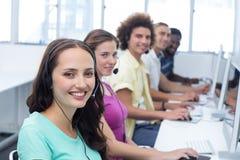 Studenti sorridenti che utilizzano le cuffie avricolari nella classe del computer Immagine Stock