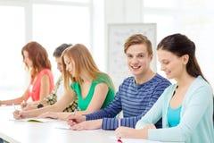 Studenti sorridenti con i manuali alla scuola Fotografie Stock
