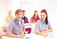 Studenti sorridenti con i taccuini alla scuola Immagine Stock Libera da Diritti