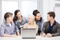 Studenti sorridenti con il computer portatile alla scuola Fotografia Stock
