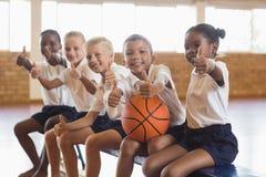 Studenti sorridenti con pallacanestro che mostra i pollici su Immagini Stock
