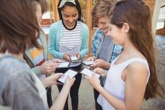 Studenti sorridenti della scuola che stanno nel cerchio e nel per mezzo del telefono cellulare Immagine Stock Libera da Diritti