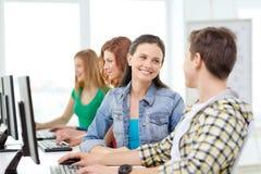 Studenti sorridenti nella classe del computer alla scuola Immagine Stock