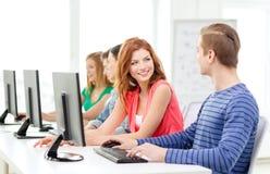 Studenti sorridenti nella classe del computer alla scuola Fotografia Stock Libera da Diritti