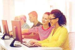 Studenti sorridenti nella classe del computer alla scuola Immagini Stock