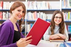 Studenti sorridenti in una biblioteca Fotografia Stock Libera da Diritti