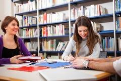 Studenti sorridenti in una biblioteca Fotografie Stock