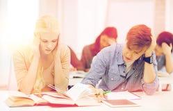 Studenti stanchi con il pc, i taccuini ed i libri della compressa Immagine Stock