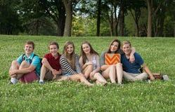 Studenti teenager che si siedono all'aperto Immagine Stock