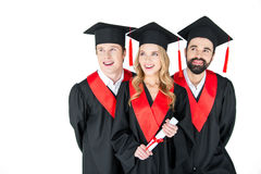 Studenti in tocchi ed abiti di graduazione che distolgono lo sguardo sul bianco Immagini Stock Libere da Diritti
