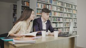Studenti in una biblioteca al computer e libro di uso della scuola e conversazione per i progetti archivi video