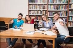 Studenti in una biblioteca che mostra i pollici su Fotografie Stock